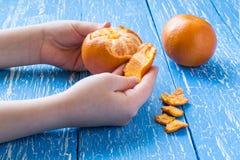 Die Hände der Kinder, die Tangerine abziehen stockbild