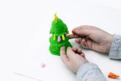 Die Hände der Kinder formen einen Pelzbaum vom Plasticine Lizenzfreie Stockfotos