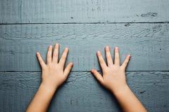Die Hände der Kinder ist auf einer hölzernen Platte Stockbild