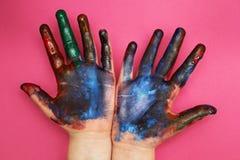 Die Hände der Kinder werden mit einer mehrfarbigen Farbe auf einem rosa Hintergrund befleckt lizenzfreies stockbild