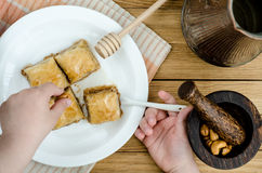 Die Hände der Kinder zu helfen, ein Baklava auf Platte zu verzieren Lizenzfreies Stockfoto