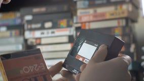 Die Hände der Männer nehmen eine VHS-Kassette aus dem Kasten heraus stock footage