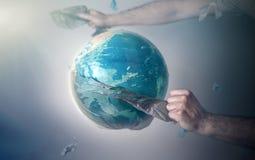Die H?nde der M?nner rei?en eine Plastiktasche von der Kugel von Planet Erde auseinander Das Konzept des Umweltschutzes eco T?nun lizenzfreies stockbild