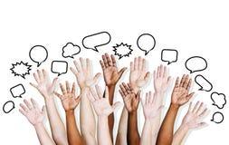 Die Hände der multi ethnischen Leute angehoben mit Sprache-Blase Lizenzfreie Stockfotografie