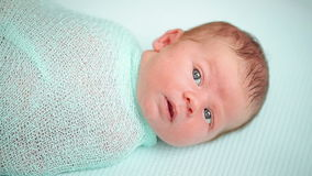 Die Hände der Mutter wickeln das neugeborene liegende Baby und stock footage