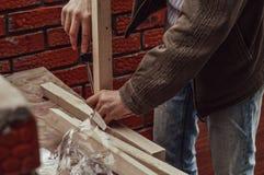 Die Hände der Nahaufnahmemänner unter Verwendung eines Schraubenziehers an der Baustelle lizenzfreie stockfotografie