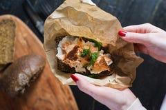 Die Hände des Chefs, der das skandinavische Sandwich mit geräuchertem Lachs auf Schwarzbrot mit Weichkäse hält lizenzfreie stockbilder