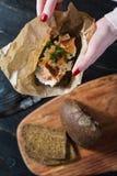 Die Hände des Chefs, der das skandinavische Sandwich mit geräuchertem Lachs auf Schwarzbrot mit Weichkäse hält stockfotografie