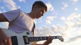 Die Hände des Gitarristen E-Gitarre spielend chords draußen und glätten, Sonnenuntergang stock footage