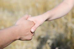 Die Hände des jungen Paares, die miteinander halten Stockfotos