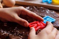 Die H?nde des Jungen schnitten Pl?tzchen vom rohen Schokoladenteig auf einem Holztisch mit bunten Buchstaben Kochen von tradition lizenzfreie stockfotos