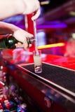 Die Hände des Kellners in der Innenstange sind gegossener Alkohol Lizenzfreies Stockbild
