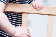 Die Hände des Kindes auf einem Brett Stockfotos