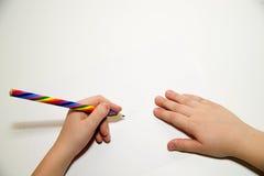 Die Hände des Kindes, die einen Bleistift an über Weiß halten Stockbild