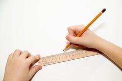 Die Hände des Kindes, die einen Bleistift an über Weiß halten Lizenzfreie Stockfotografie