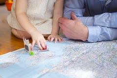 Die Hände des kleinen Mädchens und die Hände ihres Vaters auf der Karte Stockfotografie