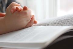 Die Hände des Kleinkindes, die auf heiliger Bibel beten Stockfotos