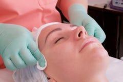Die Hände des Kosmetikers weibliches Gesicht von der überschüssigen Creme reinigen Gesichtshautpflegebehandlungen Nahaufnahme ein lizenzfreie stockfotos