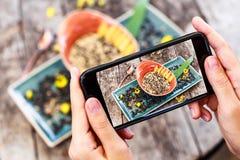Die Hände des Mädchens, die Foto des Hafermehlbreis mit Sonnenblumensamen, indischem Sesam und Pfirsichen durch Smartphone machen lizenzfreies stockbild
