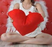 Die Hände des Mädchens, die rotes Herz im weißen Kleid mit Engelsflügeln auf rotem Hintergrund halten stockfotos
