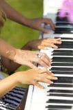 Die Hände des Mädchens und ihrer Mutter auf dem Klavier Lizenzfreies Stockbild