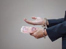 Die Hände des Mannes in den Handschellen und im Geld in seinen Palmen Stockbilder