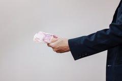 Die Hände des Mannes in den Handschellen und im Geld in seinen Palmen Lizenzfreie Stockfotografie