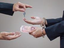 Die Hände des Mannes in den Handschellen und im Geld in seinen Palmen Lizenzfreies Stockbild