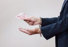 Die Hände des Mannes in den Handschellen und im Geld in seinen Palmen Stockfoto