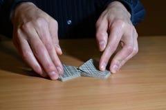 Die Hände des Mannes in der Dunkelheit beendeten, einen Satz Spielkarten, strategisches Wettbewerbskonzept des Geschäfts, Nahaufn lizenzfreie stockfotos