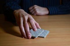 Die Hände des Mannes in der Dunkelheit setzten ein Teil Spielkarten, strategisches Wettbewerbskonzept des Geschäfts lizenzfreie stockfotografie
