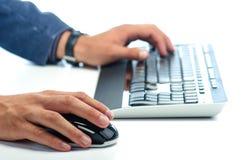 Die Hände des Mannes, die mit Computermaus und Computertastatur arbeiten Stockfotografie