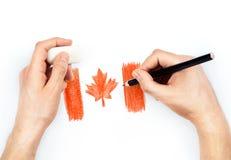 Die Hände des Mannes mit Bleistift zeichnet Flagge von Kanada auf Weiß Lizenzfreies Stockfoto