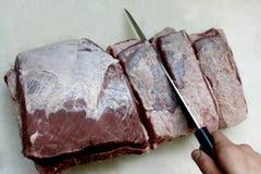 Die Hände des Mannes, die Rindfleischfleisch mit einem großen Messer auf einem weißen Schneidebrett schneiden Beschneidungspfad e stockbild