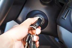 Die Hände des Mannes, zum der Schlüssel zu nehmen, um das Maschinenauto anzustellen Stockbilder