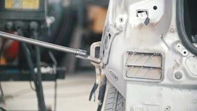 Die Hände des Mechanikers reparieren das Teil des Autos mit einem Lötkolben des Impulses stock video