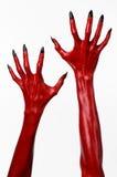 Die Hände des roten Teufels mit schwarzen Nägeln, rote Hände des Satans, Halloween-Thema, auf einem weißen Hintergrund, lokalisie Stockfoto