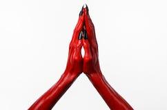 Die Hände des roten Teufels mit schwarzen Nägeln, rote Hände des Satans, Halloween-Thema, auf einem weißen Hintergrund, lokalisie Stockfotografie
