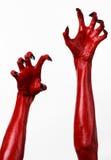 Die Hände des roten Teufels mit schwarzen Nägeln, rote Hände des Satans, Halloween-Thema, auf einem weißen Hintergrund, lokalisie Lizenzfreies Stockfoto