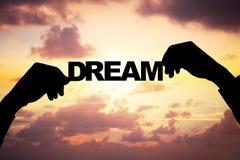 Die Hände des Schattenbildgeschäftsmannes halten Traum während des Sonnenuntergangs Stockfotografie