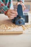 Die Hände des Tischlers unter Verwendung des elektrischen Hobels auf Holz Stockfoto