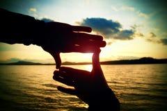 Die Hände des Zusammensetzungsfingerrahmen-Mannes nehmen Sonnenuntergang in Meer gefangen Mehrfarbiges horizontales Freienbild Lizenzfreies Stockbild