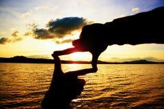 Die Hände des Zusammensetzungsfingerrahmen-Mannes nehmen Sonnenuntergang in Meer gefangen Mehrfarbiges horizontales Freienbild Stockbilder