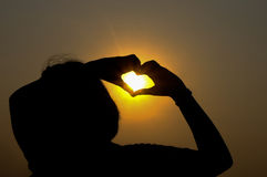 Die Hände, die ein Herz bilden, formen in den Sonnenuntergang Lizenzfreies Stockfoto