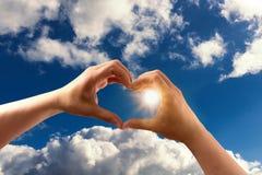 Die Hände, die ein Herz bilden, formen mit blauem Himmel Lizenzfreies Stockbild