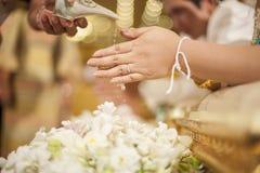 Die Hände, die Segen gießen, wässern in die Bänder der Braut, thailändisches Hochzeitscer Lizenzfreie Stockfotos