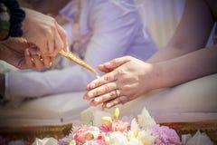 Die Hände, die Segen gießen, wässern in die Bänder der Braut, thailändisches Hochzeitscer Stockbilder