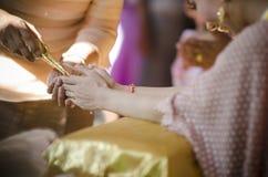 Die Hände, die Segen gießen, wässern in die Bänder der Braut, thailändisches Hochzeitscer Lizenzfreies Stockbild
