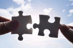 Die Hände, die versuchen, Puzzlespiel zwei zu befestigen, stellt zusammen Stockfotos