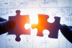 Die Hände, die versuchen, Puzzlespiel zwei zu befestigen, stellt zusammen Lizenzfreie Stockfotografie